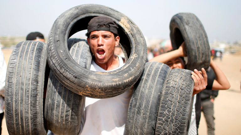 A Palestinian holds tyres at the Israel-Gaza border during a protest demanding the right to return to their homeland, east of Gaza City April 6, 2018. REUTERS/Mohammed Salem