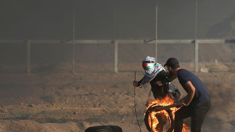 Palestinians push a burning tyre during a protest calling for lifting the Israeli blockade on Gaza and demanding the right to return to their homeland, at the Israel-Gaza border fence, east of Gaza City September 14, 2018. REUTERS/Mohammed Salem