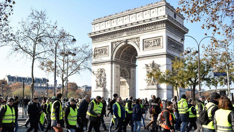Demonstrators wearing Yellow Vests (Gilets jaunes) walk past the Arc de Triomphe in Paris on November 17, 2018 during a protest against the rising of the fuel and oil prices