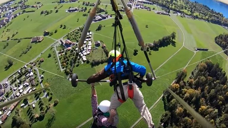 Chris Gursky who went hang gliding for the first time had to hold on for his life after his pilot forgot to strap him in