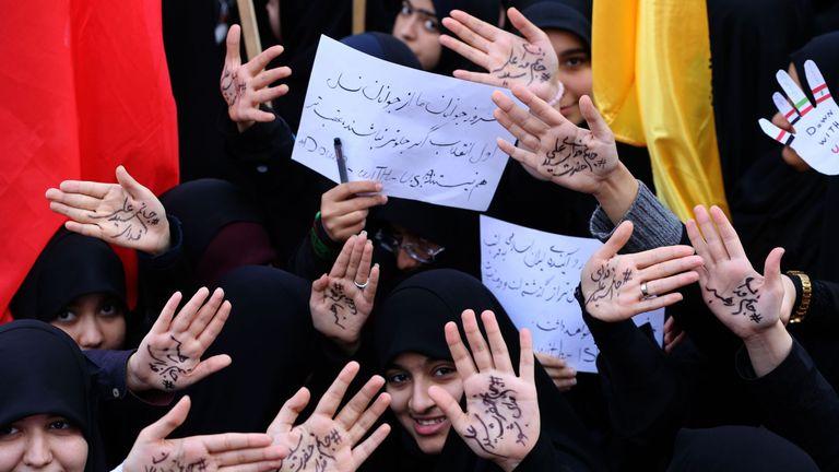 Iranian girls take part in the demonstration writing on their palms praising the Ayatollah Khamenei