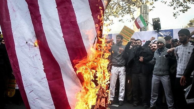 Iranian people burn the U.S. flag as they mark the anniversary of the seizure of the U.S. Embassy