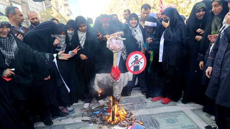 Iranian protesters burn an effigy of the US president placed on huge prints of US 100 dollar banknote