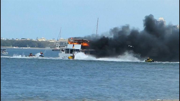 Jetskiers extinguishing houseboat fire