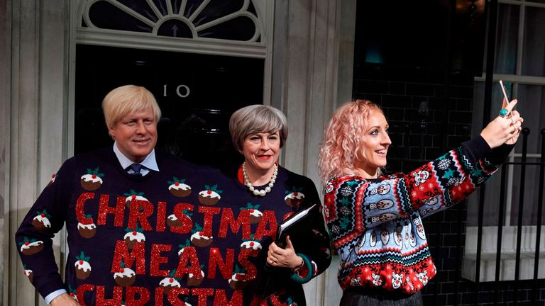 An employee (R) poses taking a selfie photograph with wax figures depicting Britain's Foreign Secretary Boris Johnson (L) and Britain's Prime Minister Theresa May (C) wearing a Christmas jumper bearing the slogan 'Christmas Means Christmas' positioned on a replica of the front step of 10 Downing Street during a photo call at Madame Tussauds in London on December 13, 2017