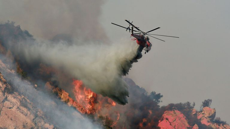 MALIBU, CA - NOV 11: A Helicopter drops flame retardant on a wildfire on November 10, 2018 in Malibu, California. (Photo by Sandy Huffaker/Getty Images)