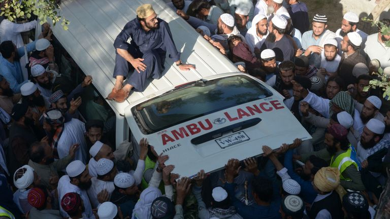 Supporters gather around the ambulance carrying Maulana Sami Ul-Haq's body during his funeral