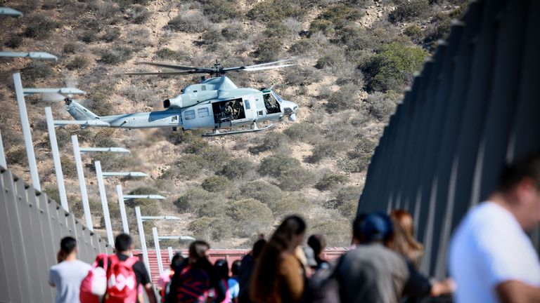 A US military helicopter flies past a pedestrian bridge after the closing of the US-Mexico border