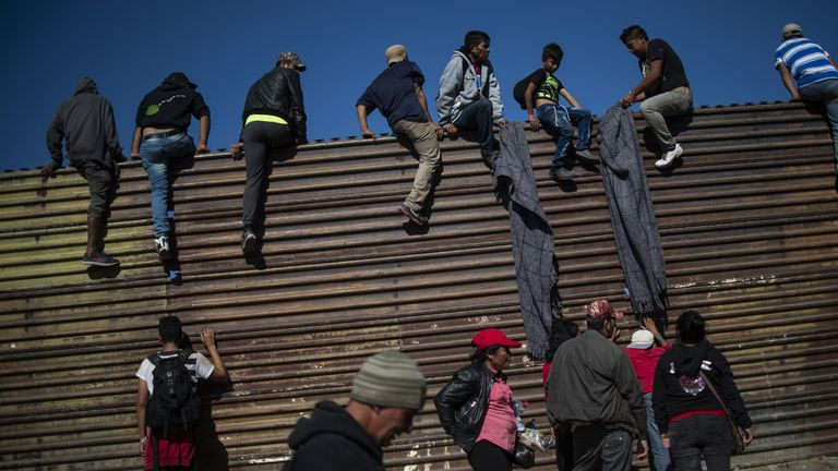 A group of Central American migrants climb the border fence between Mexico and the US