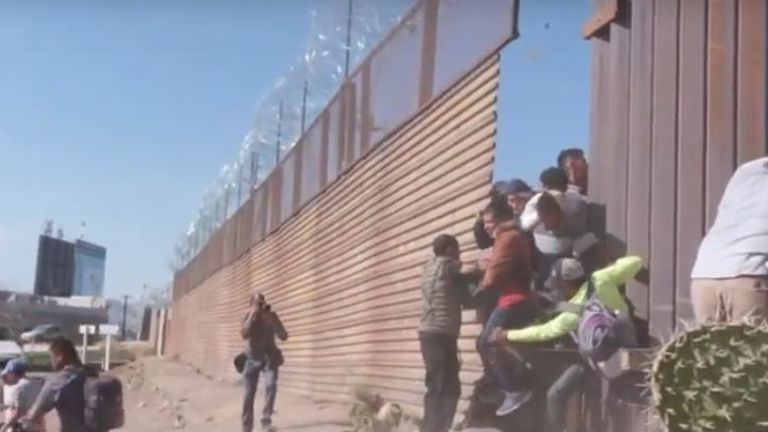 Migrants break through a small gap in a fence before US border patrol fire tear gas at them
