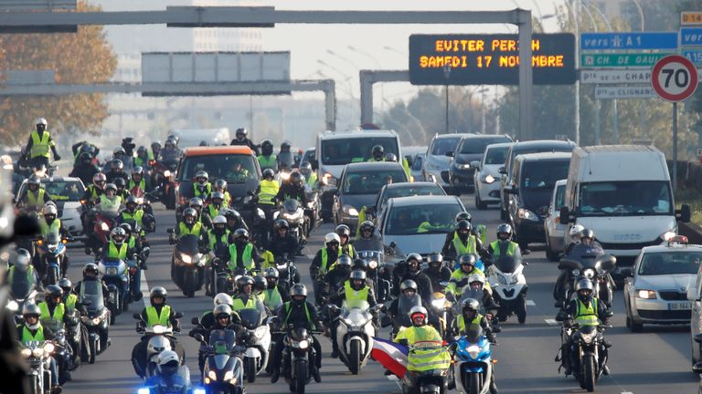 Motorcyclists wearing yellow vests, a symbol of a French drivers' protest against higher fuel prices, move a a snail's pace as they block the ring road in Paris, France, November 17, 2018