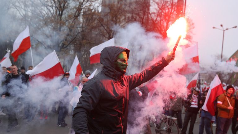 A masked participant celebrates the 100th anniversary of the reinstatement of Polish independence