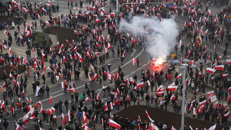 A participant lights a flare among people bearing Polish flags