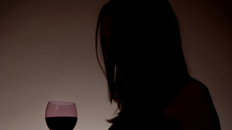 An eight-month pregnant woman holding a glass of wine, London