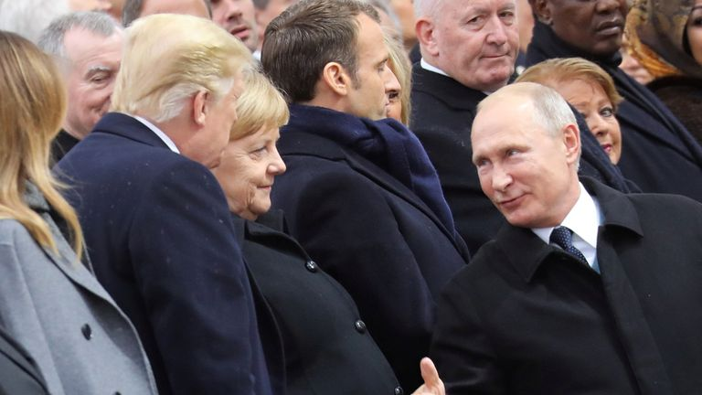 Russian President Vladimir Putin talks with German Chancellor Angela Merkel and U.S. President Donald Trump as they attend a commemoration ceremony for Armistice Day, 100 years after the end of the First World War at the Arc de Triomphe, in Paris, France, November 11, 2018.