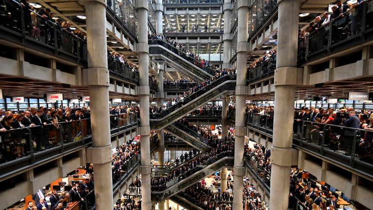 Workers stand during a Remembrance Service at the Lloyd's building in London