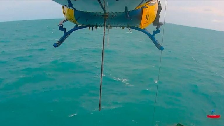 Man is airlifted to safety after spending a night on a capsized catamaran off the coast of Queensland