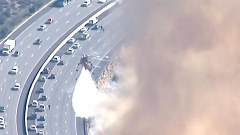 Fire crews attempt to extinguish blaze alongside southern California freeway
