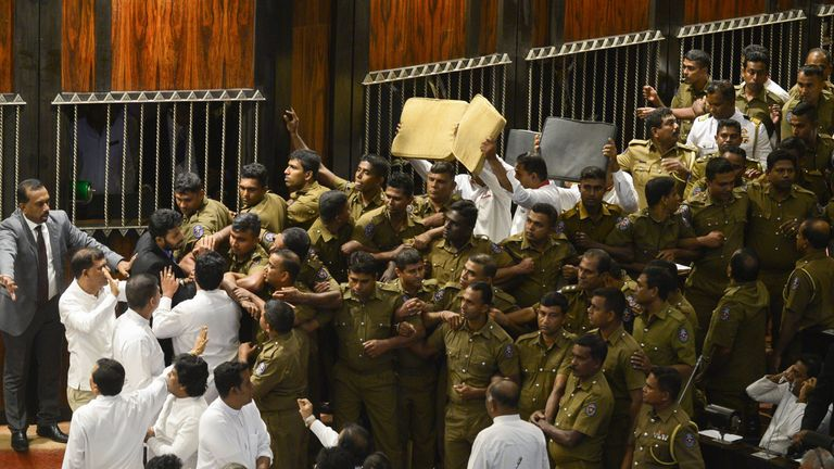 Sri Lankan police try to take their positions to escort parliament speaker Karu Jayasuriya into the assembly hall in Colombo on November 16, 2018. - Sri Lanka's parliamentary speaker required police protection as violence returned to the legislature for a second day November 16, with rival factions in the island's constitutional crisis showing no signs of backing down. A group of legislators occupied speaker Karu Jayasuriya's chair for 50 minutes and he was only able to take his seat after he en