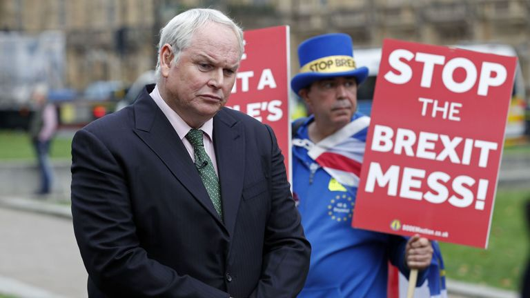 Sky News reporter Adam Boulton attracts the unwanted attention of Anti-Brexit campaigner Steve Bray (R) outside the Palace of Westminster in central London on November 15, 2018, as inside lawmakers discuss the draft withdrawal agreement negotiated between the European Union and the United Kingdom