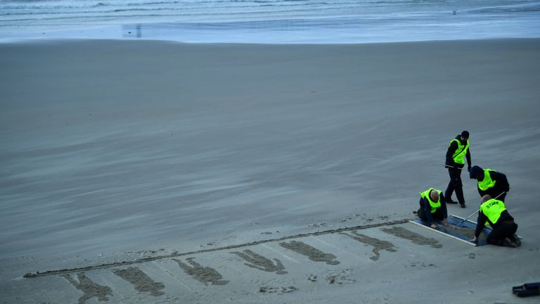 Volunteers rake the sand as they draw depictions of those who fell
