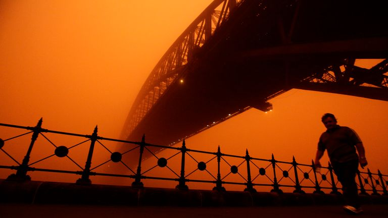 A pedestrian walks under the Sydney Harbour bridge as a dust storm blankets the city September 23, 2009