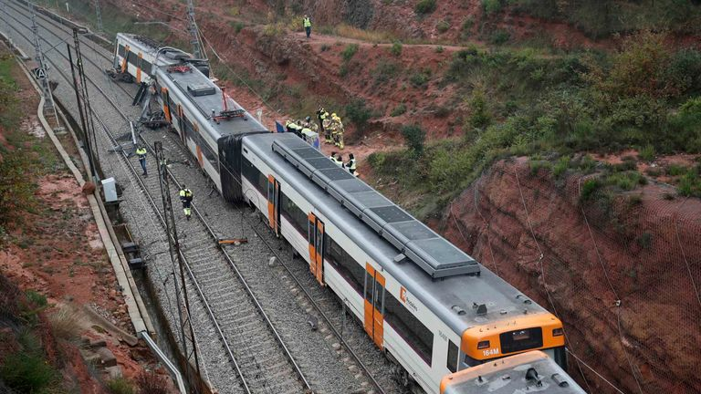 Rescue workers survey the scene after a commuter train derailed between Terrassa and Manresa, outside Barcelona, Spain