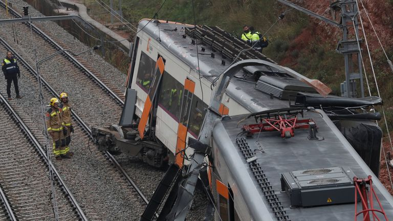 Rescue workers survey the scene after a commuter train derailed between Terrassa and Manresa, outside Barcelona