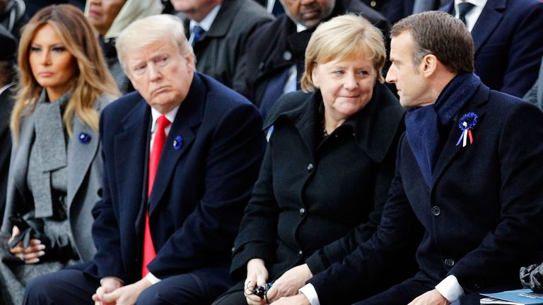 French President Emmanuel Macron (R) touches the knee of German Chancellor Angela Merkel (2nd R) as they sit next to US President Donald Trump (2nd L) and US First Lady Melania Trump (L) during a ceremony at the Arc de Triomphe in Paris on November 11, 2018 as part of commemorations marking the 100th anniversary of the 11 November 1918 armistice, ending World War I