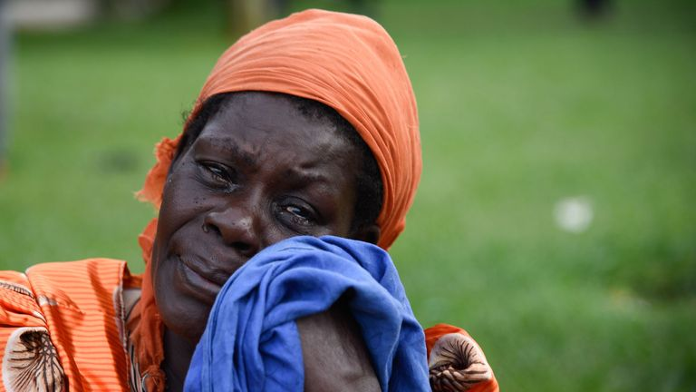 A woman sheds tears at the rescue site of capsized cruise boat on Lake Victoria