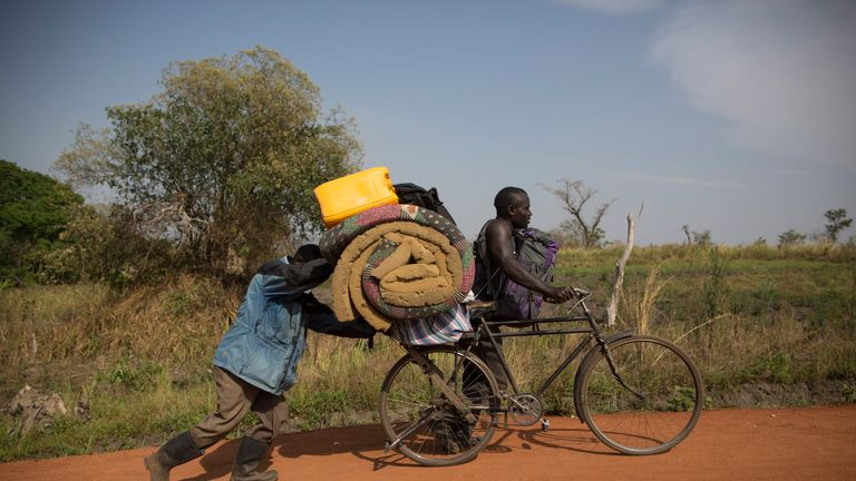 South Sudanese refugees pushing their belongings after crossing into Uganda