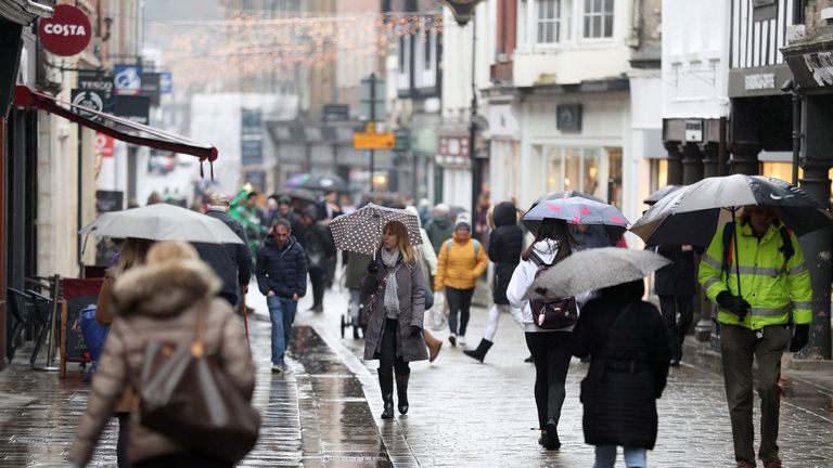 Shoppers brave the rain as they make their way down the High Street in Winchester, Hampshire
