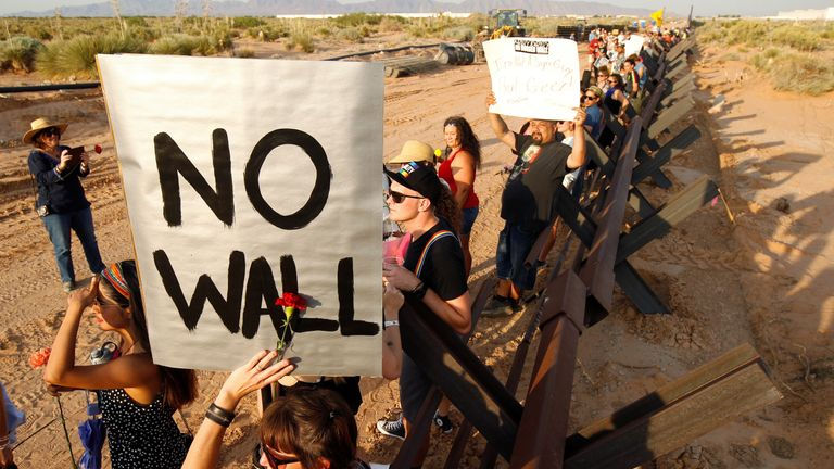 Demonstrators hold up placards during a protest against the border wall in New Mexico