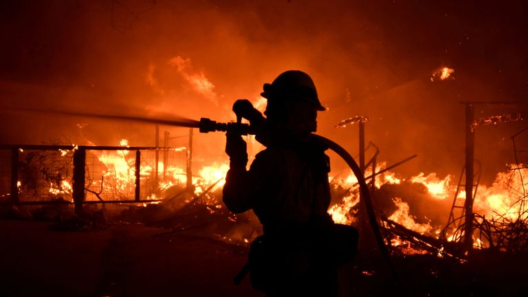 A firefighter hoses down a property engulfed in flames during the Woolsey Fire in Malibu, California, U.S. November 9, 2018. REUTERS/Gene Blevins