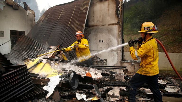 Firefighters work hot spots as the Woolsey Fire continues to burn in Malibu, California, U.S. November 10, 2018