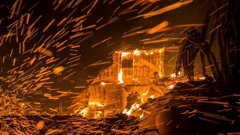 Strong winds blow embers from burning houses during the Woolsey Fire on November 9, 2018 in Malibu, California