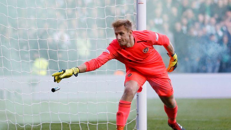 Hearts goalkeeper Zdenek Zlamal went down under a challenge from a fan