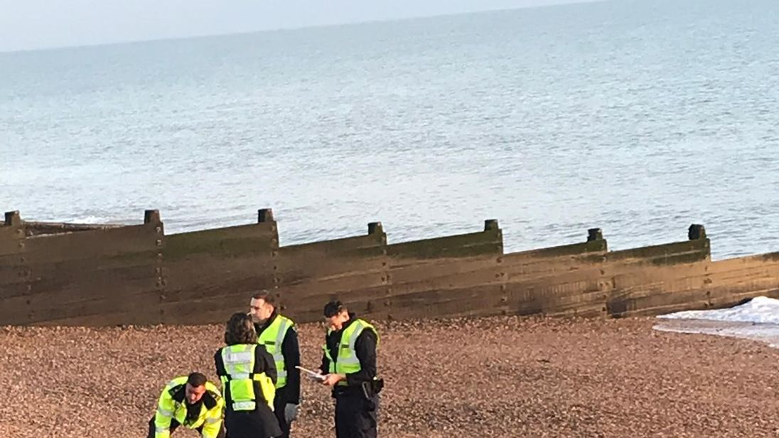 Border officials and an inflatable dinghy on the beach at Kingsdown, Kent
