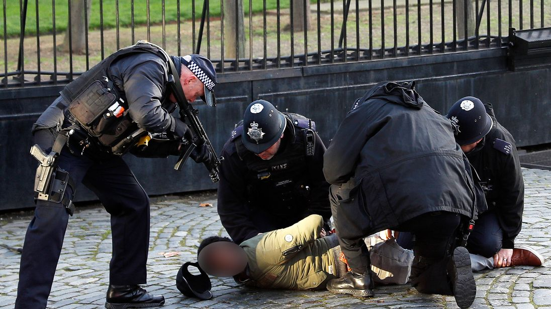 Armed police restrain a man inside the grounds of the Houses of Parliament