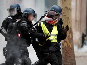 French police detain a protester during clashes in Paris