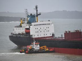 A tug boat works to help refloat the Kuzma Mini