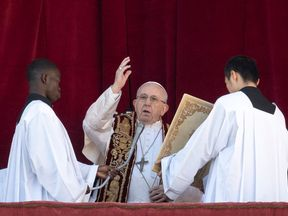 Pope Francis (C) blesses from the balcony of St Peter's basilica during the traditional 'Urbi et Orbi' message to the city and the world