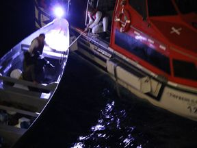 Two fishermen are rescued by the crew of the Empress Of The Seas. Pic: Jared L. Eberle