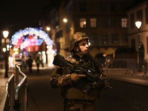 An armed soldier stands guard outside the Christmas market after a shooting