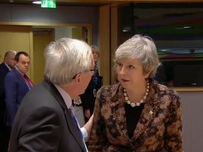 Theresa May speaks with Jean-Claude Juncker at the EU summit