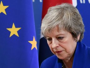 TOPSHOT - Britain's Prime Minister Theresa May leaves after a press conference following a special meeting of the European Council to endorse the draft Brexit withdrawal agreement and to approve the draft political declaration on future EU-UK relations on November 25, 2018 in Brussels. - The European Union's top official urged British lawmakers to ratify the Brexit deal Prime Minister Theresa May has negotiated with European leaders, warning it will not be modified. 'This is the best deal possib