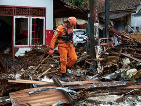 A rescue worker walks through the rubble from houses destroyed by a tsunami on December 23, 2018 in Carita, Indonesia