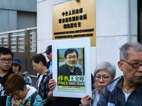 Activists hold a placard (C) of detained Chinese human rights lawyer Wang Quanzhang at a rally outside the Chinese Liaison Office in Hong Kong