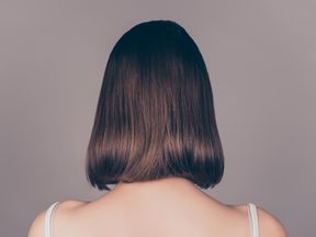 Back view of young beautiful wonam with short symmetric hair isolated on gray background