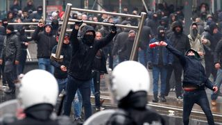 Far-right supporters throw barricades during a protest in Brussels